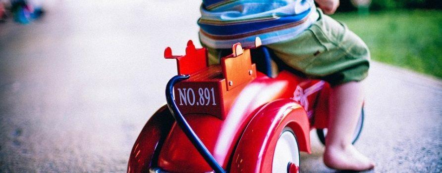 Dziecko jadące na trójkołowym rowerze. Zdjęcie z dużym zbliżeniem na którym widać tylko fragment dziecka.