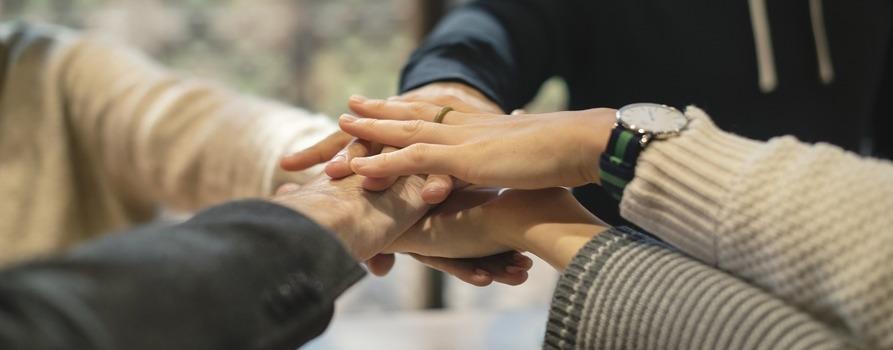Ręce pięciu osób splecione razem. Fotografia jest wykadrowana na same ręce wspomnianych osób.