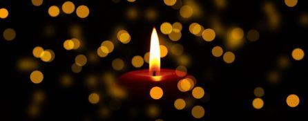 Świeca na czarnym tle, wokół wiele odblasków innych świec.
