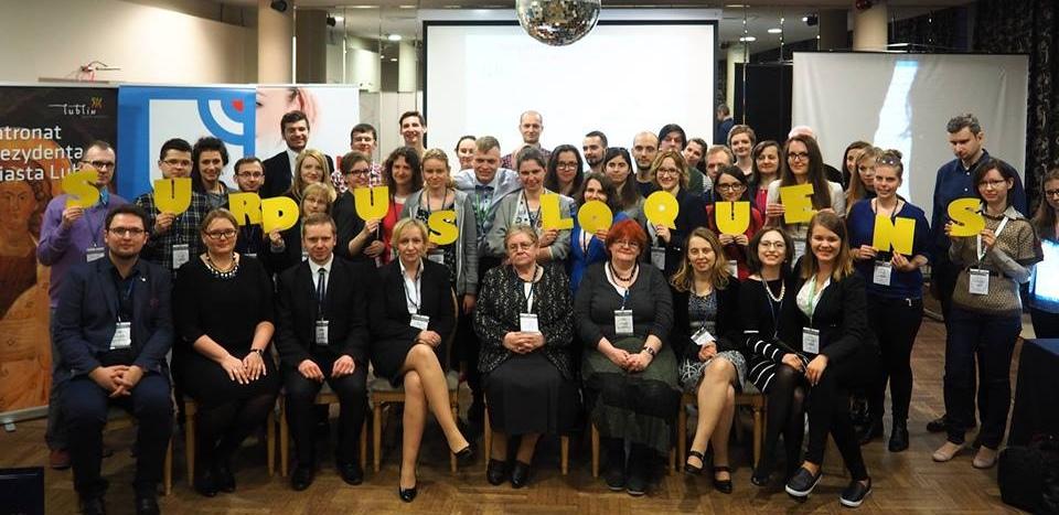 Zdjęcie przedstawiające grupę ludzi, gości konferencji. Część osób trzymając w rękach żółte litery tworzy napis: SURDUS LOQUENS
