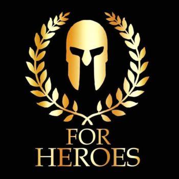Logotyp Fundacji For Heroes. Logotyp ma kształt kwadratu, który jest czarnym tłem. Pierwszy plan zajmuje złota przyłbica a otacza ją wianek ze złotych liści. Pod spodem widnieje złoty napis For Heroes. Całość nawiązuje do motwu gladiatorów.