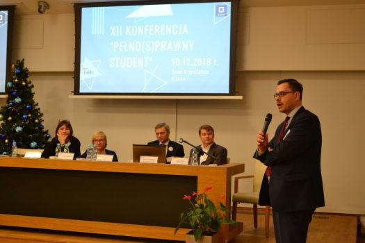 zdjęcie przedstawia najważniejszych prelegentów podczas konferencji pełno(s)prawny student 2018. Jeden mężczyzna stoi i przemawia do innych.
