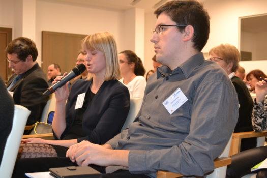 Zdjęcie przedstawia studentkę mówiącą przez mikrofon podczas konferencji pełno(s)prawny student 2018. Obok niej siedzą inni uczestnicy.