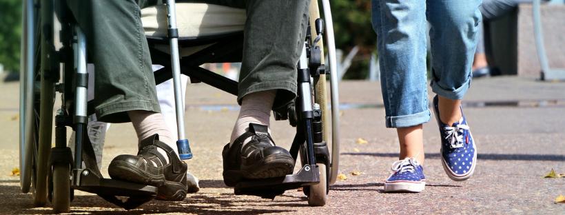 dwie osoby na ulicy, jedna jest na wózku inwalidzkim, obok niej idzie druga osoba. Widzimy tylko ich nogi.
