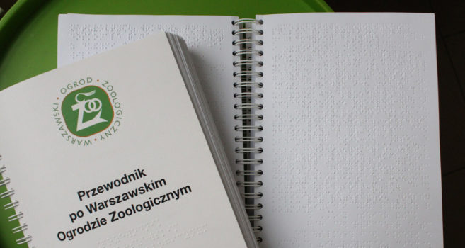 na zdjęciu widoczna jest książka zapisana językiem Braille'a. To jest przewodnik po warszawskim ogrodzie zoologicznym dla osób niewidomych i słabowidzących.