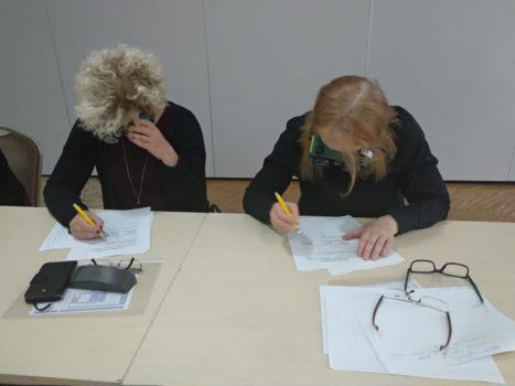 zdjęcie przedstawia dwie kobiety, blondynki, które są pochylone nad kartkami papieru. To uczestniczki szkolenia bliżej dostępności, które rozwiązują zadanie dotyczące barier architektonicznych w codziennym życiu.