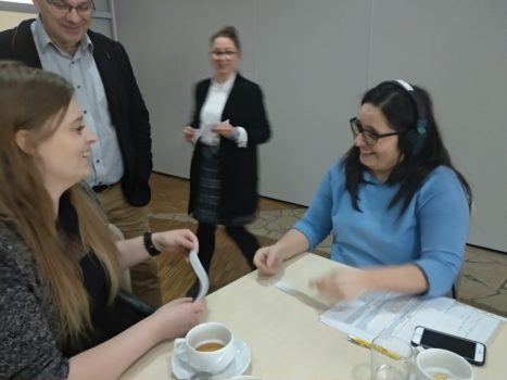 dwie kobiety na pierwszym planie, jedna ma słuchawki, druga nie. Trzymają kartki i otwarcie, z uśmiechem chcą się porozumiewać między sobą. W tle są dwie osoby - kobieta oraz mężczyzna - to trenerzy podczas szkolenia z bliżej dostępności.