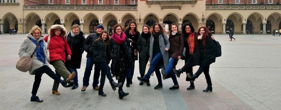 zdjęcie przedstawia grupę ludzi - kobiet i mężczyzn na tle Sukiennic w Krakowie, kilka osób podnosi nogi jakby chcieli kopać piłkę