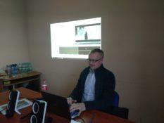 zdjęcie przedstawia mężczyznę. Siedzi przy biurku, ma niebieską koszulę, okulary. Przed nim stoi komputer. Spogląda na ekran komputera i jest skoncentrowany. Palcami porusza po klawiaturze. Za nim w tle jest ściana, na której wyświetla się obraz z komputera. To jeden z prowadzących szkolenie z audiodeskrypcji.