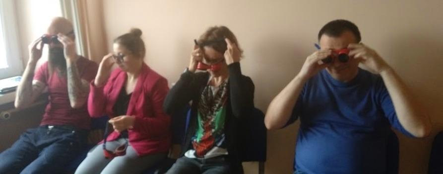 zdjęcie przedstawia grupę uśmiechniętych czterech osób, dwóch mężczyzn oraz dwie kobiety. Nakładają specjalne okulary, są wyraźnie tym zaciekawieni. Wszyscy siedzą. To szkolenie z audiodeskrypcji.