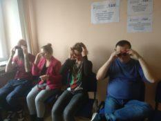 Zdjęcie przedstawia cztery osoby - dwie kobiety i dwóch mężczyzn. Wszyscy siedzą. Nakładają okulary. Są wyraźnie zaciekawieni.