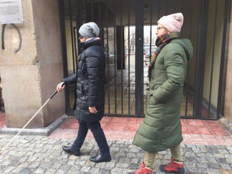 zdjęcie przedstawia dwie kobiety - jedna z laską i opaską na oczach, drugą idącą obok. Obie są na ulicy. To ćwiczenia  w ramach projektu z echolokacji.