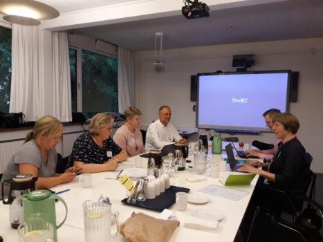 zdjęcie przedstawia grupę osób, kobiet i mężczyzn. Siedzą przy stole i rozmawiają. To uczestnicy szkolenia z echolokacji.
