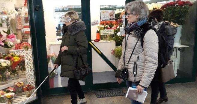zdjęcie przedstawia dwie kobiety, jedna jest w opasce na oczach oraz trzyma laskę. Druga ma notatnik oraz aparat fotograficzny. Obie idę obok sklepów.