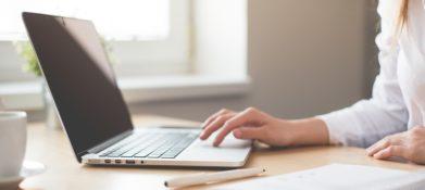 zdjęcie przedstawia stół, na którym leży laptop. Na klawiaturze są palce młodej kobiety, sprawiają wrażenia jakby pisała.