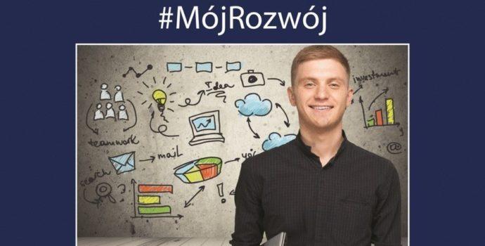 zdjęcie przedstawia młodego mężczyznę - studenta, który stoi na tle kolorowej tablicy z różnymi napisami. W tle jest napis Mój rozwój. To plakat programu płatnych praktyk Mój rozwój, organizowanego przez Ministerstwo Inwestycji i Rozwoju