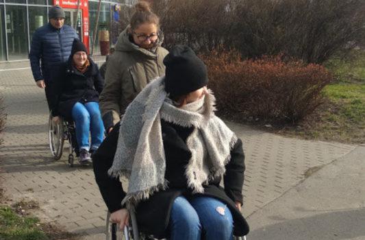 zdjęcie przedstawia cztery osoby. Trzy z nich to kobiety, dwie z nich są na wózkach. To wiosenny dzień, wszyscy ubrani są ciepło, choć jedna osoba nie ma już czapki. Osoby na wózkach to uczestnicy szkolenia Bliżej dostępności, którzy doświadczają barier architektonicznych podczas ćwiczenia. Wspierają ich nasi trenerzy.