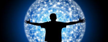 zdjęcie przedstawia czarną sylwetkę człowieka, który obejmuje glob ziemski. Glob przypomina jedną wielką kulę, z wieloma połączeniami i światłami. Można sobie wyobrazić, że tak działa połączenie internetowe.