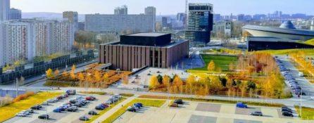 zdjęcie przedstawia część Katowic z loty ptaka. Można zobaczyć parkingi z samochodami, fragment stadionu Spodka, budynki biurowe. Pomiędzy nimi są jesienne piękne drzewa.