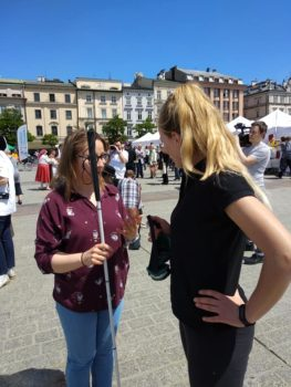 dwie młode kobiety - jedna trenerka naszej fundacji i druga - w czarnej koszuli podczas ćwiczenia, jak asystować osobie niewidomej