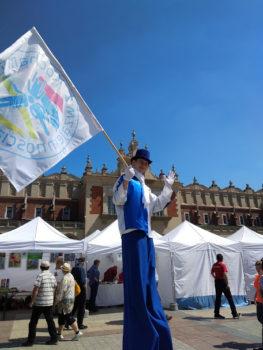 Mężczyzna na szczudłach, w biało-niebieskim stroju z flagą Kocham Kraków z wzajemnością podczas inauguracji XX tygodnia osób z niepełnosprawnościami