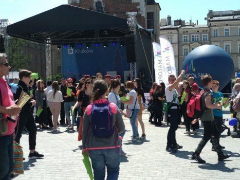 krakowski rynek podczas inauguracji XX tygodnia osób z niepełnosprawnościami. Wiele osób przechodzi, kilka stoi przed sceną.