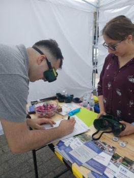 mężczyzna w specjalnych okularach, które symulują wadę wzroku, próbuje wypełnić wniosek o dowód osobisty. Podczas inauguracji XX tygodnia osób z niepełnosprawnościami w Krakowie.