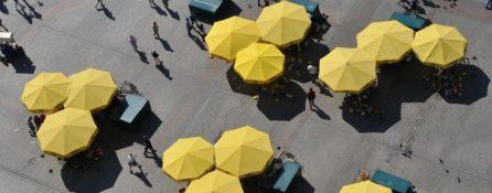 z lotu ptaka pokazane żółte duże parasole na rynku miasta. Pomiędzy nimi chodzą ludzie, poruszają się po gładkiej, równej nawierzchni.