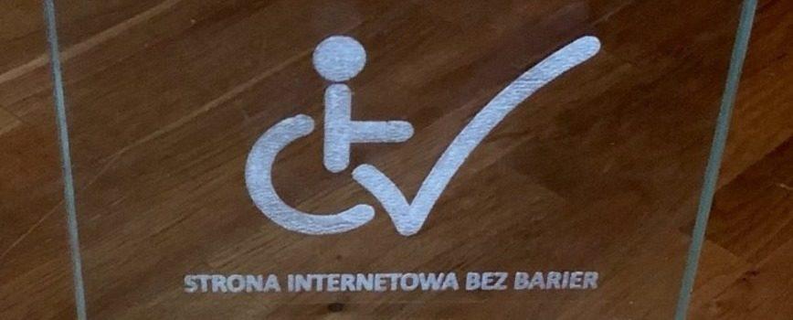 na ciemnym tle biały znak osoby z niepełnosprawnością, siedzącej na wózku. W koło wchodzi znaczek akceptacji - jakby ptaszek. To fragment nagrody dla naszego pracownika Mikołaj Skotnickiego w konkursie strona internetowa bez barier. Zdjęcie pochodzi z serwisu http://a11y.report/
