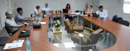 grupa uczestniczek i uczestników międzynarodowego projektu AWCAT podczas spotkania w Warnie, w Bułgarii. Wszyscy siedzą przy stole, a komputery stoją przed nimi.