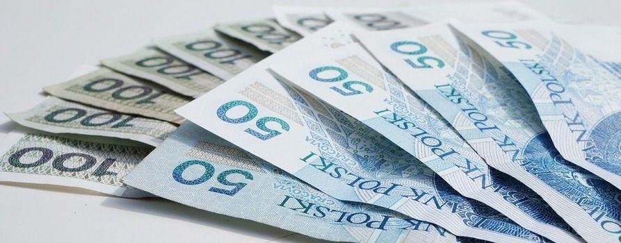 banknoty pięćdziesięcio i stuzłotowe rozłożone w wachlarz na powierzchni symbolizują świadczenie