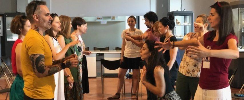"""grupa ludzi, kobiety i mężczyźni, ubrani w letnie stroje - stoją w dwóch rzędach na przeciwko siebie. Wykonują ruchy rękami. Patrzą sobie prosto w oczy, sprawiają wrażenie jakby sobie coś wyjaśniali przy pomocy gestów. To uczestnicy warsztatów z dostępności miejsc kultury, jakie odbyły się we włoskiej Perugii, w ramach projektu """"OHAS - Opening Heritage and Art Sites for People with Special Needs""""."""