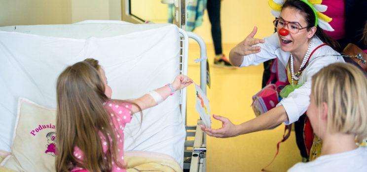 w szpitalnym pokoju na łóżku siedzi mała dziewczynka, wyciąga rękę jakby bardzo chciała po coś sięgnąć. Przed nią jest młoda kobieta z czerwonym sztucznym nosem w dużych okularach, śmieje się, gestykuluje. To clown z fundacji Czerwone Noski. A zdjęcie ilustruje zaproszenie na szkolenie dla wolontariuszy - śmiech leczy.