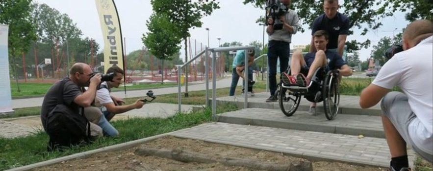 zdjęcie przedstawia młodego mężczyznę siedzącego na wózku, który prowadzi drugi mężczyzna. Obaj starają się zjechać schodami, są skoncentrowani. Przed nimi jest kolejna bariera - drewniane bale w piasku. Obok stoją fotografowie oraz operator kamery.