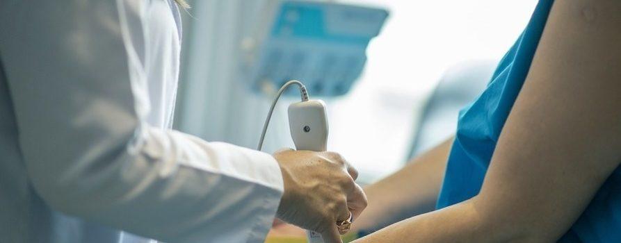 zdjęcie przedstawia dwie osoby lekarza oraz starszą kobietę. Kobieta siedzi, na zdjęciu są widoczne jej ręce. Druga osoba bada ją, dotykając przegubów jej dłoni. To ilustracja do informacji o dofinansowaniu na zdrowie.