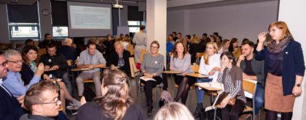 duża grupa uśmiechniętych ludzi - zarówno kobiet, jak i mężczyzn siedzi w sali - są podczas warsztatów które odbyły się w czasie czwartego kongresu osób z niepełnosprawnościami