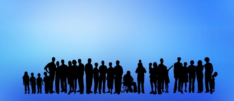 grupa sylwetek na niebieskim tle, różne osoby młode, starsze, dzieci stoją w jednej zwartej grupie, wśród nich jest też osoba na wózku. To ilustracja do piątego już spotkania środowiska osób z niepełnosprawnościami