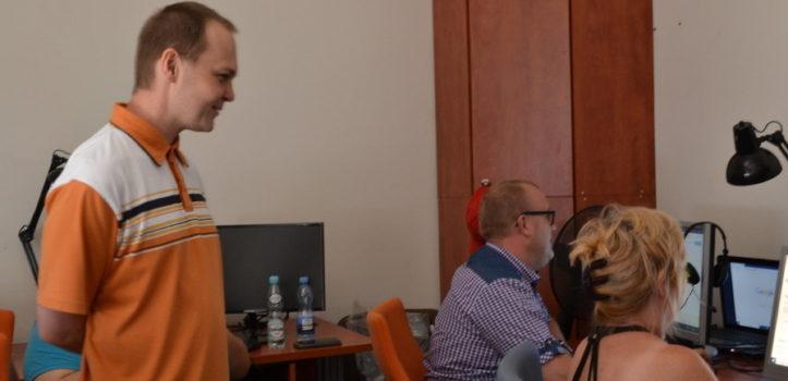 trzy osoby w sali komputerowej, jeden mężczyzna stoi i coś mówi do dwójki innych - kobiety i mężczyzny siedzących przy komputerach. To zdjęcie ze szkolenia informatycznego w naszej Fundacji.