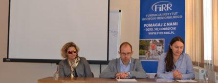 zdjęcie przedstawia Justynę Kucińską, prezeskę Fundacji instytut rozwoju regionalnego, Krzysztofa Kurowskiego, przewodniczącego Polskiego forum osób niepełnosprawnych oraz Annę Trzmiel, koordynatorkę projektu w ramach którego był zrealizowany IV kongres osób z niepełnosprawnościami. Wszystkie osoby siedzą przy stole. To konferencja prasowa kończąca projekt.