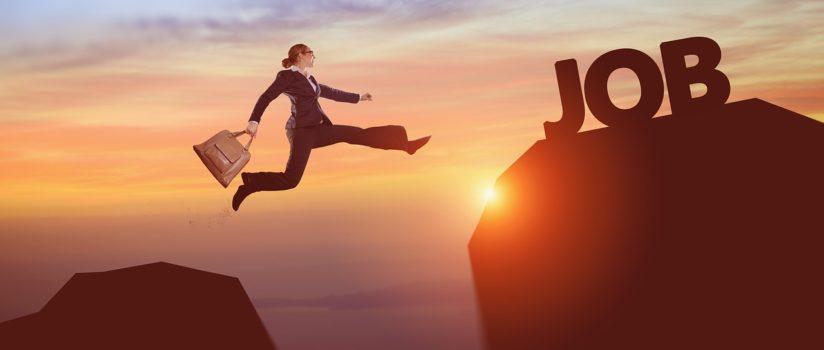 w świetle zachodzącego słońca kobieta przeskakuje w powietrzu z góry na drugą górę. W tel jest napis job czyli praca. To ilustracja do zapytania ofertowego związanego z projektem jaki realizuje nasza fundacja