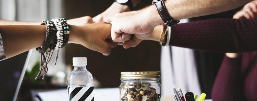 na zdjęciu cztery pary rąk złożonych w pięści uderzają się w geście sukcesu. To ilustracja do naszego zapytania ofertowego związanego z projektem jaki realizujemy.