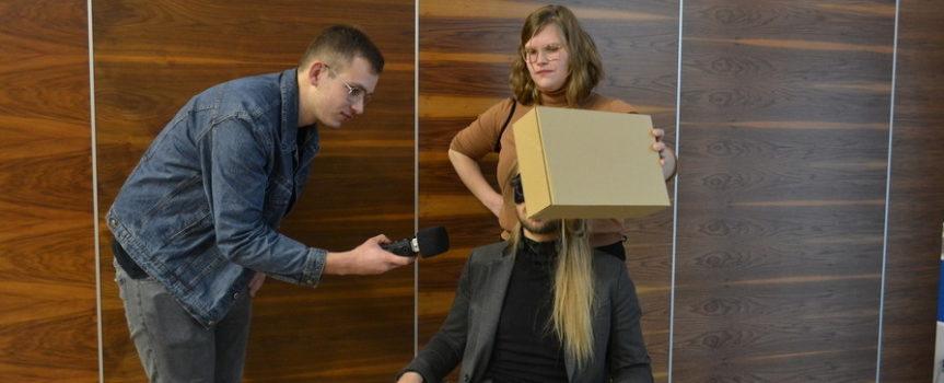 kilka osób, mężczyzna z mikrofonem pochyla się nad osobą siedzącą na krześle. Osoba siedząca ma przed swoją twarzą tekturowe pudełko, które trzyma stojąca za nią młoda kobieta. To jedno z ćwiczeń warsztatów z echolokacji
