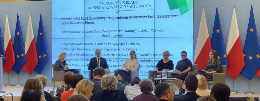zdjęcie przedstawia grupę osób siedzących w dużej sali, po lewej stronie stoją stojaki z flagami Polski oraz Unii Europejskiej, w tle jest duży slajd z informacją o tym, jaki jest temat rozmowy - restart zawodowy. najtrudniejszy pierwszy krok. Zawsze jest pora na własny biznes. Na tle tego zdjęcia siedzi kilka osób, kobiety i mężczyzna, jedną z kobiet k=jest Joanna Bryk, wiceprezeska naszej fundacji, która prowadziła tę dyskusję