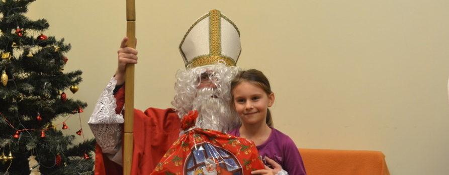 mała dziewczynka z prezentem w dużej paczce siedzi na kolanach świętgo Mikołaja. Obok widać choinkę. Siedzą na pomarańczowej sofie. To zdjęcie ze spotkania ze świętym Mikołajem w naszej Fundacji.