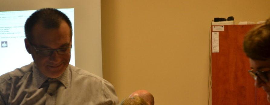 Na zdjęciu stoi uśmiechnięty mężczyzna, bardzo się cieszy. To Artur Then nasz trener podczas odbierania certyfikatu szkolenia z tekstów łatwych.