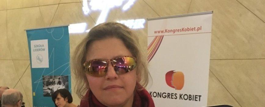 Justyna Kucińska, prezeska naszej Fundacji podczas III Kongresu Praw Obywatelskich. Ubrana w czarną marynarkę oraz bordowy szal, trzyma w ręku tablicę z napisem: działam bo zmiana sama się nie zrobi