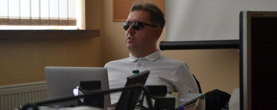 Piotr Witek siedzi przy biuru w naszej fundacji. Przed nim stoi komputer. Piotr prowadzi szkolenie dla naszego zespołu z dostępności dokumentów