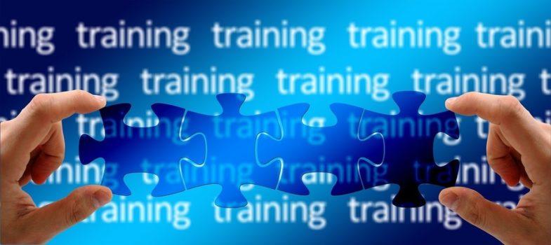 na niebieskim tle ułożone są puzzle, dwie dłonie układają je w jeden wzór. To ilustracja zapytania ofertowego organizacji szkoleń w ramach projektu dostępna administracja publiczna szkolenia dla kadry