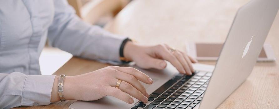 dłonie kobiety na klawiaturze komputera, palce jakby się poruszały.