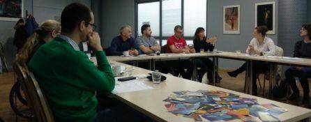 grupa ludzi, kobiety i mężczyźni siedzą wokół stołu, rozmawiają. To uczestnicy szkolenia z bliżej dostępności